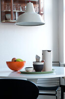 Metal lamp above round dining table with designer kitchen utensils