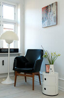 Black leather armchair next to floor lamp and order table