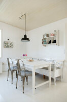 Metal chairs and bench on the wooden table in the dining room in white