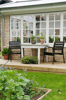 Black chairs at a table on a terrace in front of the brick house with lattice windows