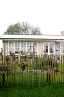 Picket fence in front of a house with a summer garden