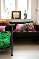 A plastic basket on a metal table in front of a leather sofa with patchwork cushions