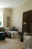 Living room in natural tones with an old door and wine jugs as decoration