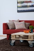 Pallet furniture on casters as a coffee table in front of the red sofa