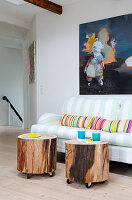 Homemade side tables made of tree slices on furniture castors in front of a sofa