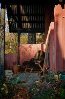 Covered terrace and chair with fur on the red wooden house in autumn