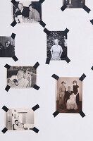 Black and white photos with black masking tape on the wall