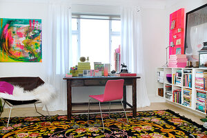 Pink chair in front of a wooden desk in a study