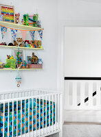 Shelves with toys above the crib in the white nursery