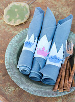 Homemade napkin rings with small crowns on blue napkins