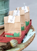 Paper bags with gift tags and crowns on a red metal tray