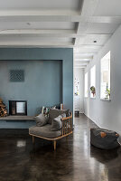 Cosy chair on concrete floor in front of fireplace with blue wall