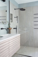 A shower area with a glass partition next to a washbasin