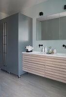 A grey cupboard next to a washbasin