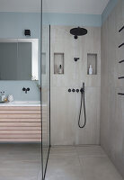 Shower area with glass partition next to washstand