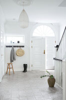 Wooden stool, coat rack, and boots in the hallway with staircase