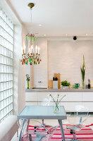 Transparente Stühle am Glastisch in moderner Wohnküche