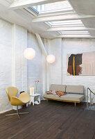 Sessel und Sofa im Durchgangszimmer mit Dachfenstern und Backsteinwänden