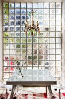 Bunter Kronleuchter überm Esstisch an der Glasbausteinwand