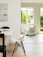 A designer chair at a dining table in front of a passage to the living room with access to the garden