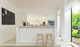 Bar stools at a kitchen counter next to an open garden door