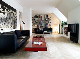 Black leather couch and red coffee table in the open living room, bookshelf in the background