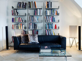 Black leather couch and glass table in front of an open wall shelf in the living room