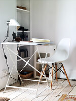 A filigree folding table and a white chair in the corner of a room