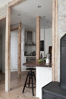 A breakfast bar with bar stools in an open-plan kitchen with wooden supports