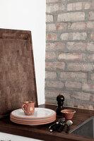 Geschirr auf Holzarbeitsplatte vor Ziegelwand