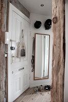 Weiße Eingangstür mit verschiedenen Schlössern und Wandspiegel im Eingangsbereich mit rustikalen Holzstützen