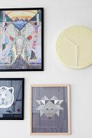 Bilder und Uhr an weißer Wand
