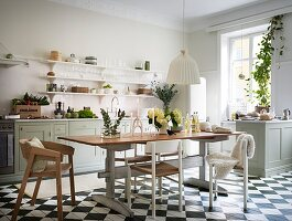 Table with different chairs in a classic kitchen with a checkerboard floor