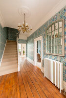 Blue-patterned Art Nouveau wallpaper in hallway with board floor