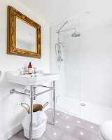 Sink below gilt-framed mirror and shower with glass screen in bathroom