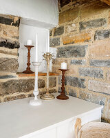 Candlesticks on low sideboard in rustic niche