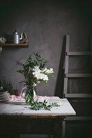 Weisser Blumenstrauss mit Blättern in Glasvase auf Marmortisch