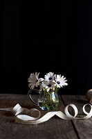 Weisse Blumen in Glasvase auf Holztisch mit Band