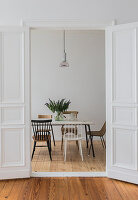 Minimalist dining room seen through open double doors