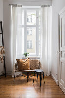 Cushion on bench and stool in front of tall period-apartment windows