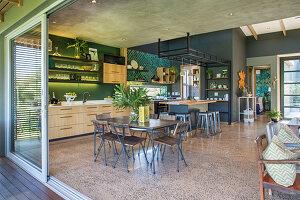 Großer offener Wohnraum im Industriestil in Grau und Grün