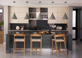Barhocker an der Kücheninsel vor moderner Küche in Grautönen