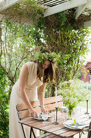 Woman wearing wreath of flowers on head setting table below pergola
