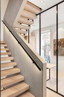 Indirekte Beleuchtung am Geländer einer Treppe mit offenen Stufen