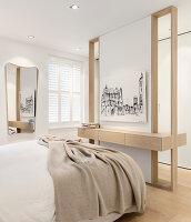 Bild an der modernen Trennwand vorm Bett im Schlafzimmer
