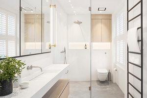 Modenes helles Bad mit klarer Linie und Glaswand zur Dusche