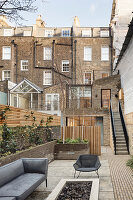 Grey seating on terrace in courtyard surrounded by urban brick houses