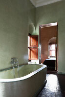 Masonry bathtub in Mediterranean bathroom with green walls