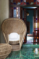 Cane peacock chair on terrace outside open stained-glass doors