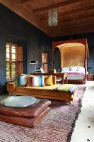 Himmelbett und gelbe Recamiere im orientalischen Schafzimmer